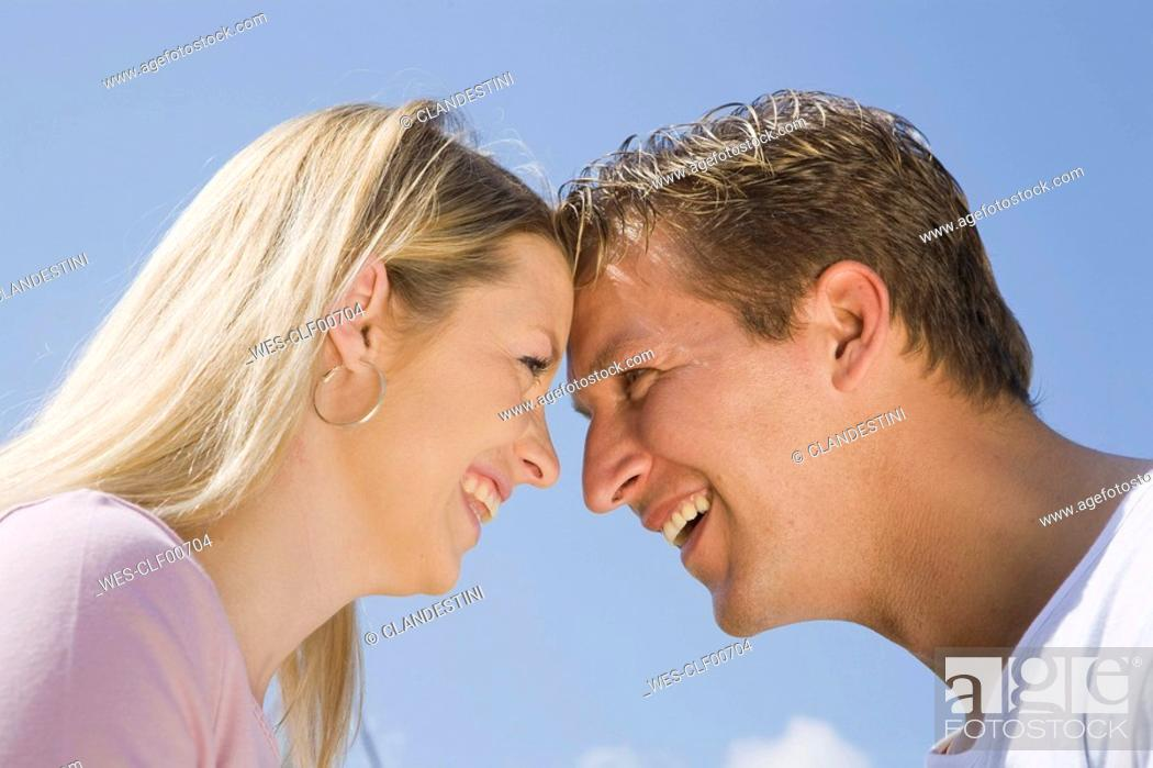 Stock Photo: Germany, Bavaria, Munich, Young couple head to head, smiling, side view, portrait.