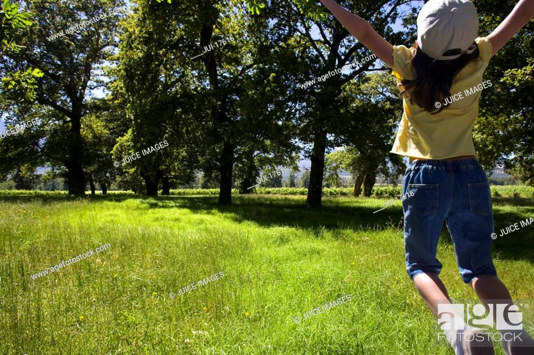 Stock Photo: Girl jumping in field.