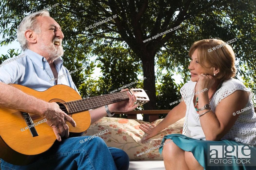 Stock Photo: Senior man playing a guitar in front of a senior woman.