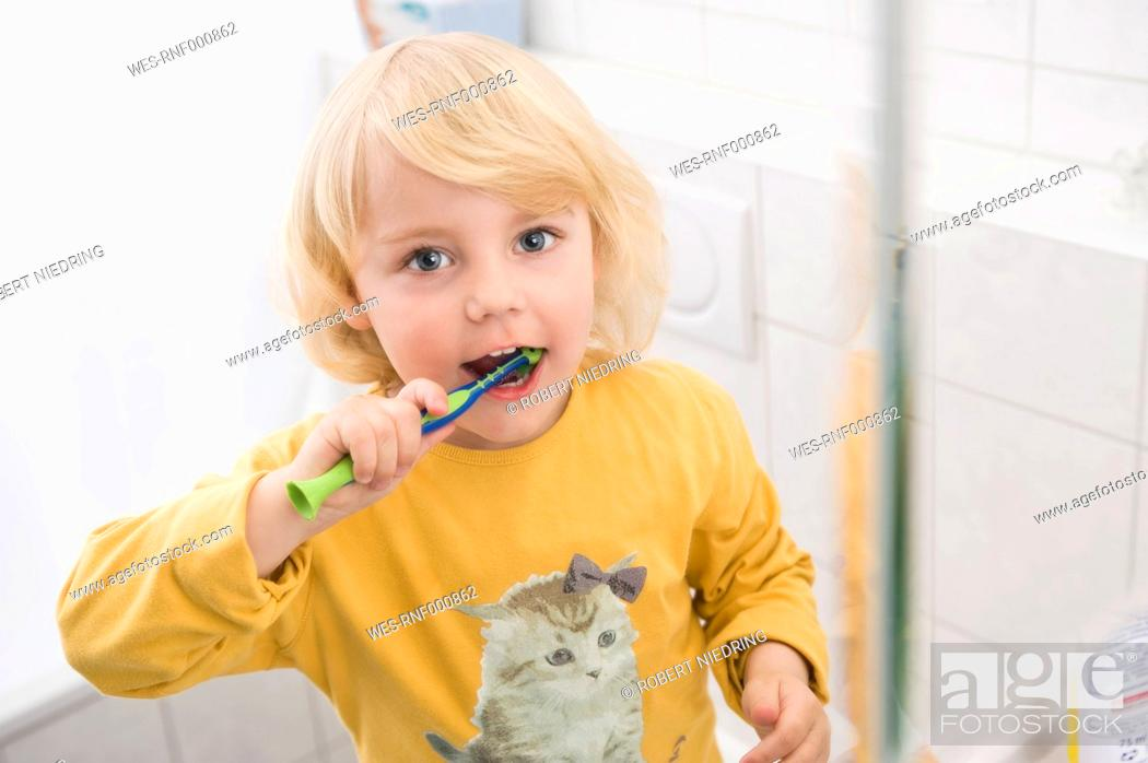 Stock Photo: Girl brushing her teeth in bathroom, close up, portrait.