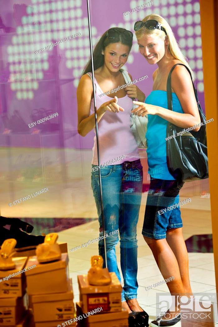 Stock Photo: Young women looking through shop window.