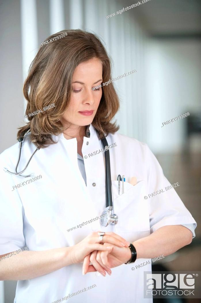 Stock Photo: Female doctor checking the time.