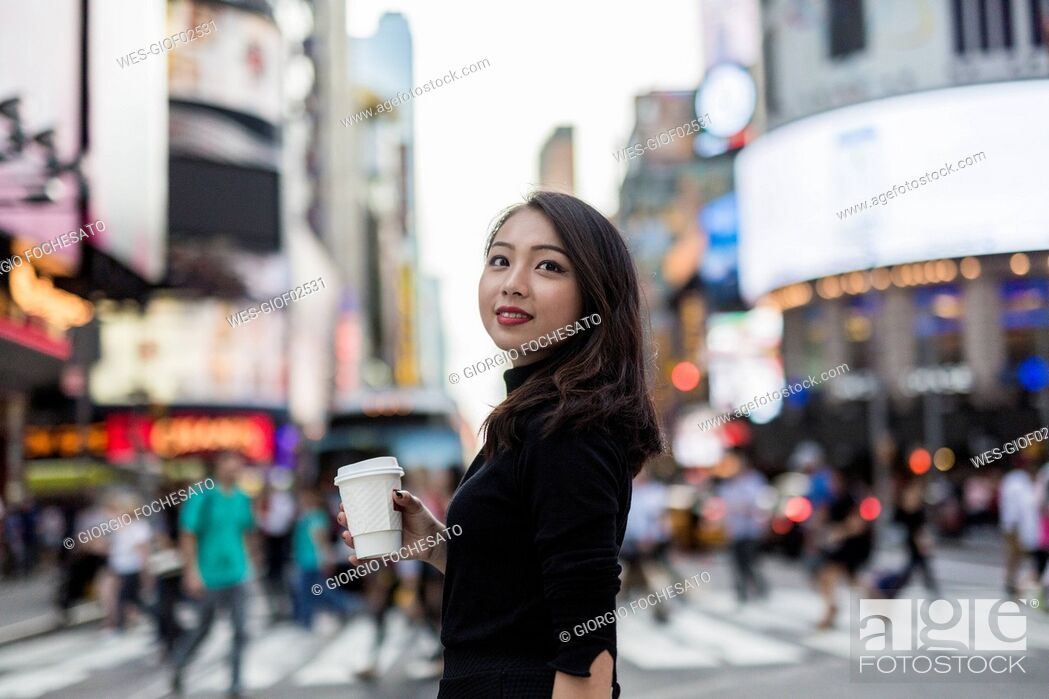 Stock Photo: USA, New York City, Manhattan, young woman with coffee to go on the street.