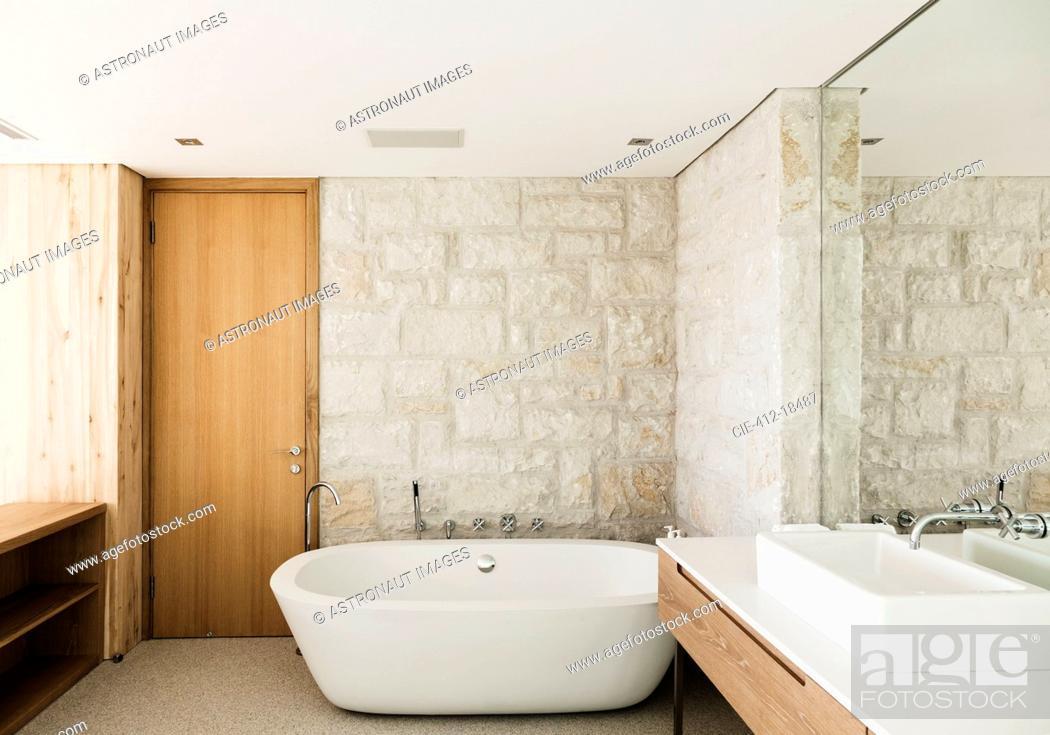 Stock Photo: Stone walls behind soaking tub in modern bathroom.