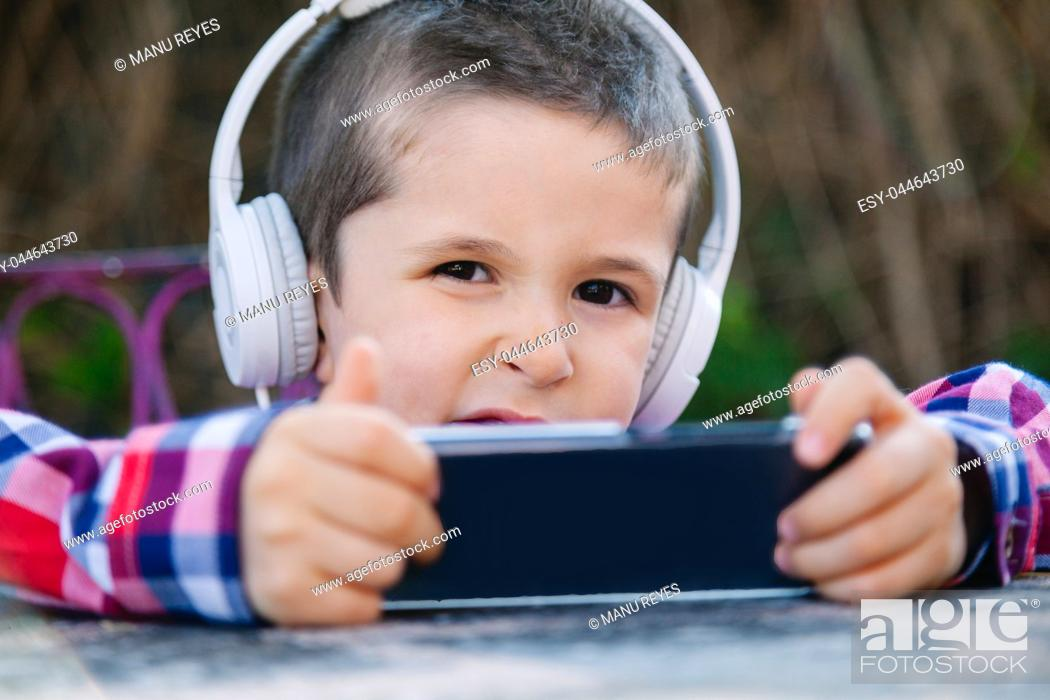 Stock Photo: boy listening to music with withe headphones on the outside.