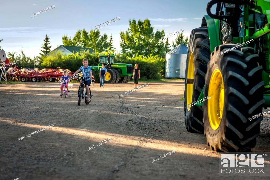 Stock Photo: Children riding bicycles beside a large tractor on the family farm as the parents stand watching in the background; Herschel, Saskatchewan, Canada.