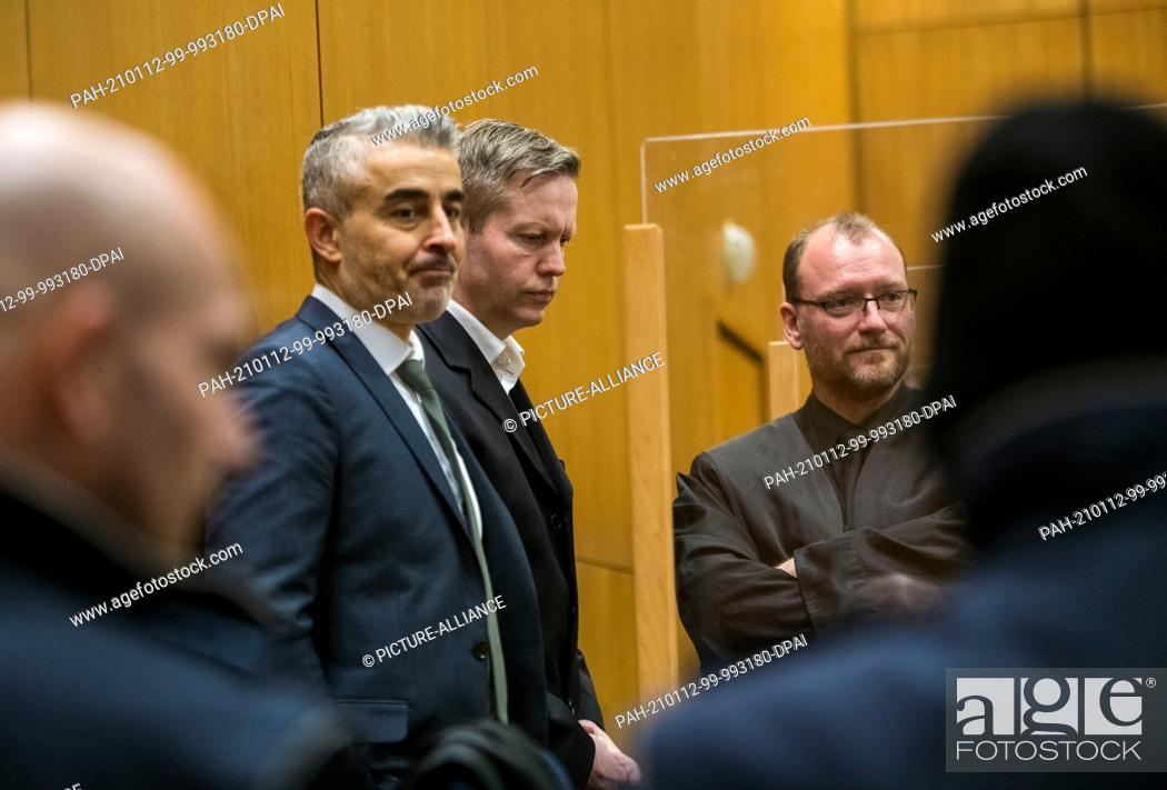 Stock Photo: 12 January 2021, Hessen, Frankfurt/Main: The main defendant Stephan Ernst (M) stands between his lawyers Mustafa Kaplan (l) and Jörg Hardies in a courtroom of.