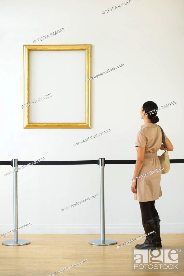 Imagen: Woman looking at blank picture frame in art gallery.