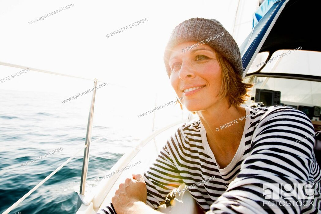 Stock Photo: Smiling woman standing on boat.