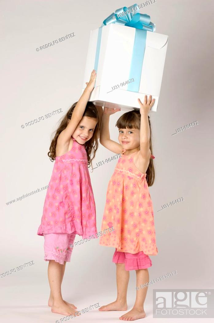 Stock Photo: Four year old twins with a big present in a studio setting.
