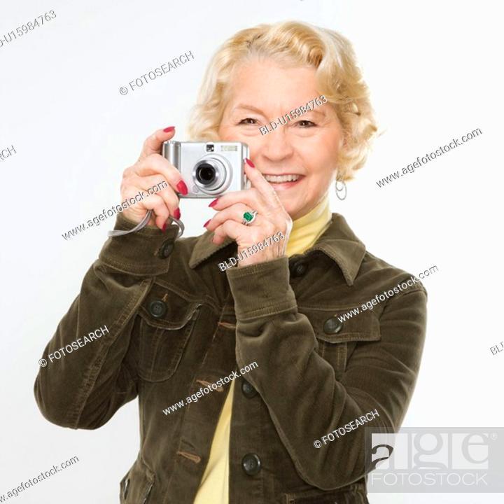Stock Photo: Caucasian senior woman taking photo with digital camera of viewer.