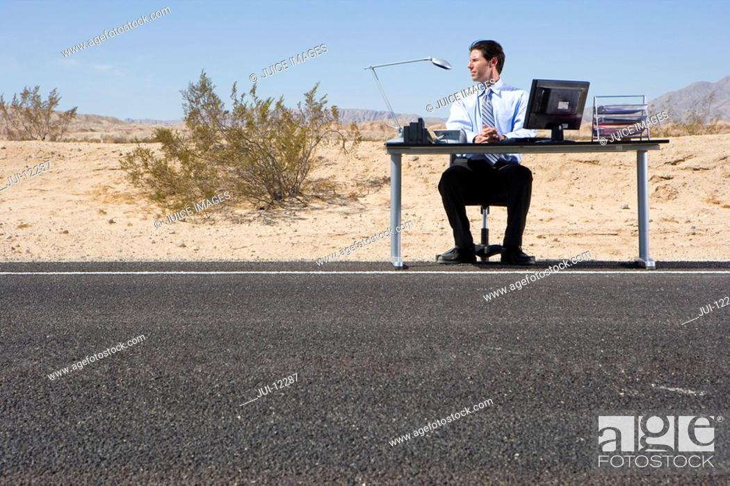 Stock Photo: Businessman at desk on side of road in desert, low angle view.