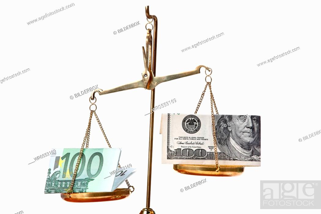 Imagen: Euro notes and dollar on scales.Isolated against a white background.