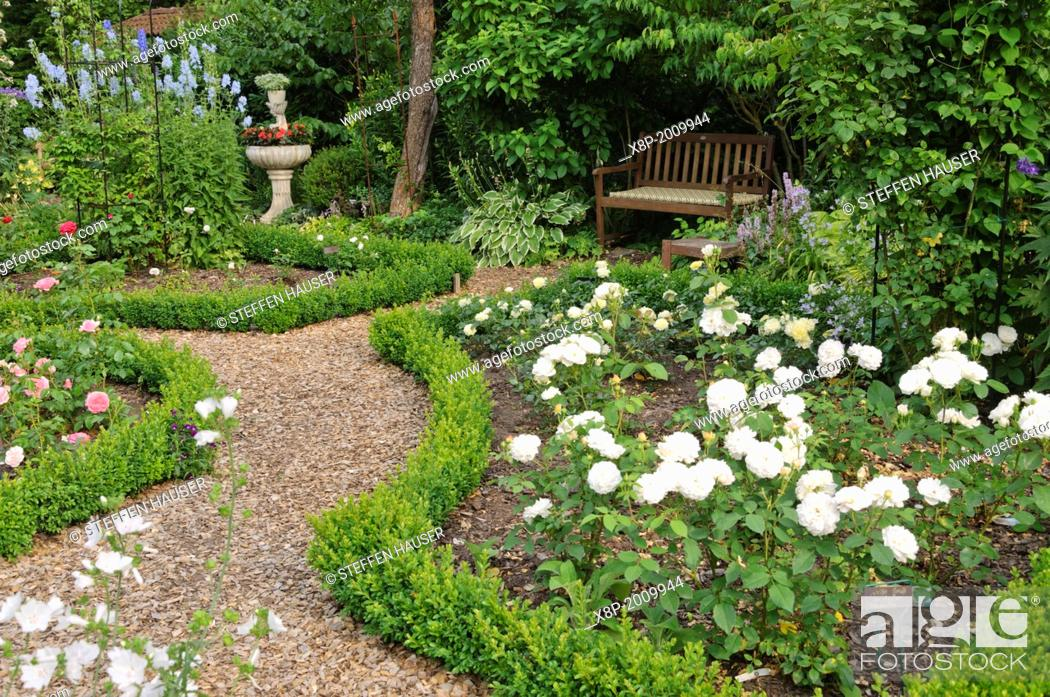 Stock Photo: Rose garden with box hedges, planted fountain and seating area. Design: Marianne and Detlef Luedke.