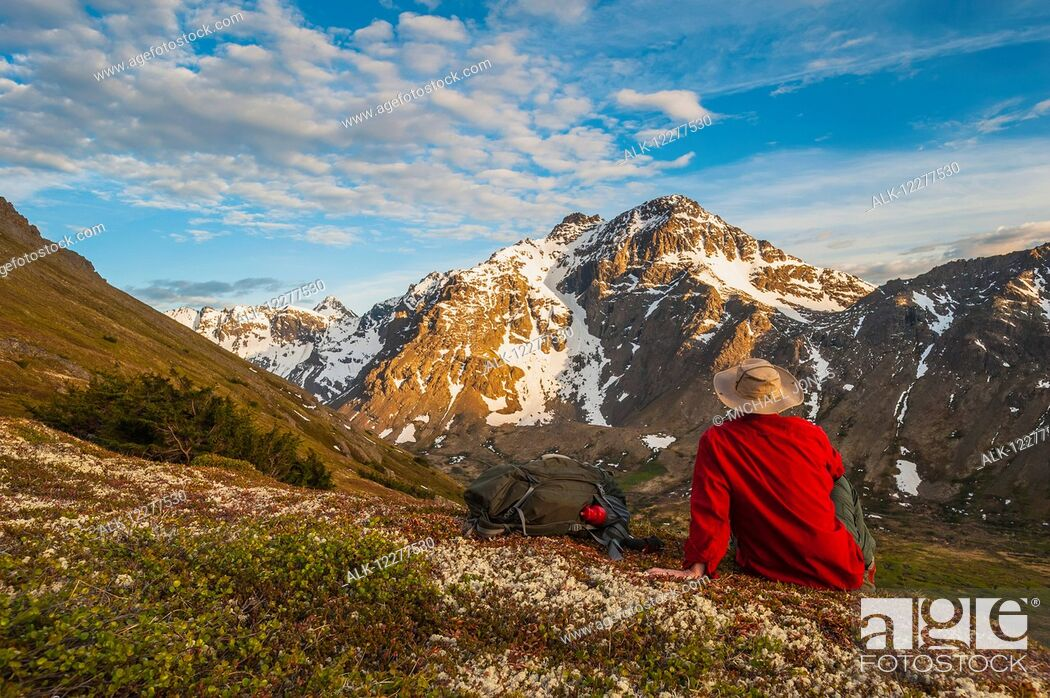 Imagen: Hiker rests on a hillside overlooking Powerline Pass valley and trail, Chugach State Park, Southcentral Alaska.