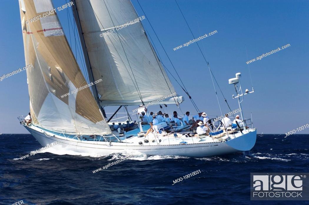 Stock Photo: Crew sitting on sailboat on ocean.