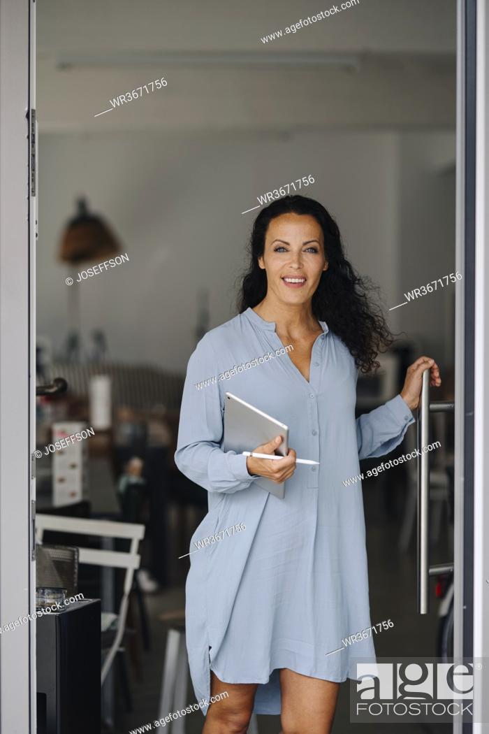 Stock Photo: Smiling female owner standing at entrance of coffee shop.