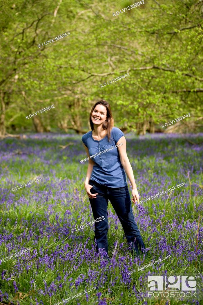 Stock Photo: A young woman standing in the woods, holding a bunch of bluebells, laughing.