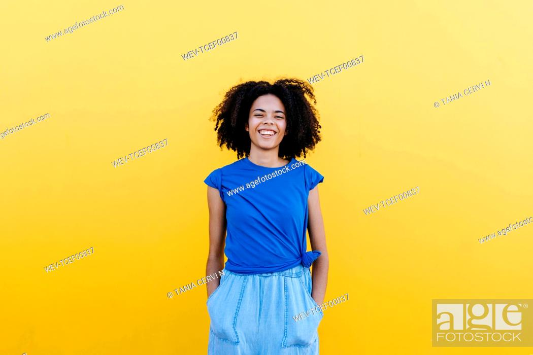 Stock Photo: Pretty woman standing in front of yellow wall, smiling happily.