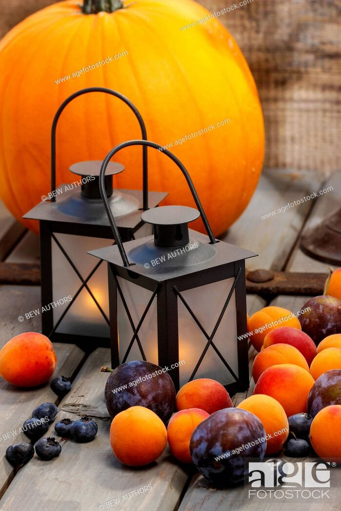 Imagen: Autumn fruits and traditional lanterns on wooden table. Seasonal decoration.