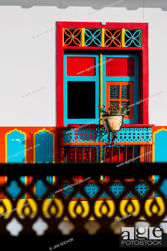 Stock Photo: A brightly painted wooden balcony is seen in the first floor of a colonial house in Jardín, a village in the coffee region (Zona cafetera) of Colombia.