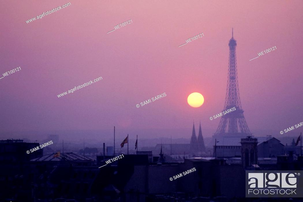 Stock Photo: Silhouette of the Eiffel Tower surrounded by rooftops at sunset, Paris, France.