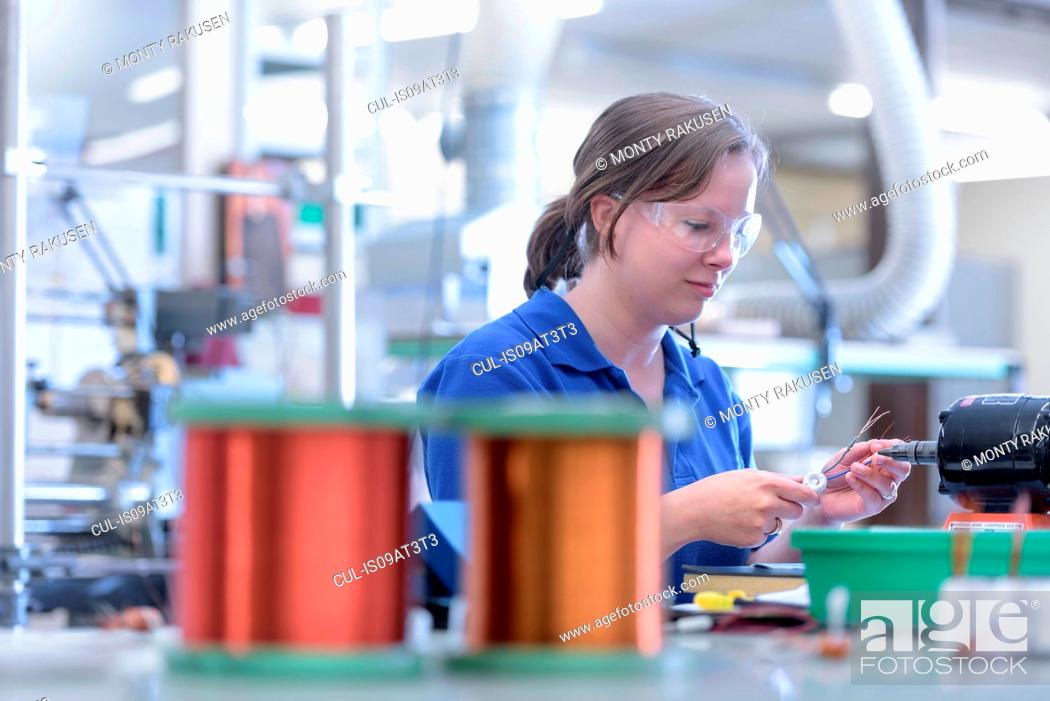 Stock Photo: Female worker assembling electromagnetic coils in electronics factory.