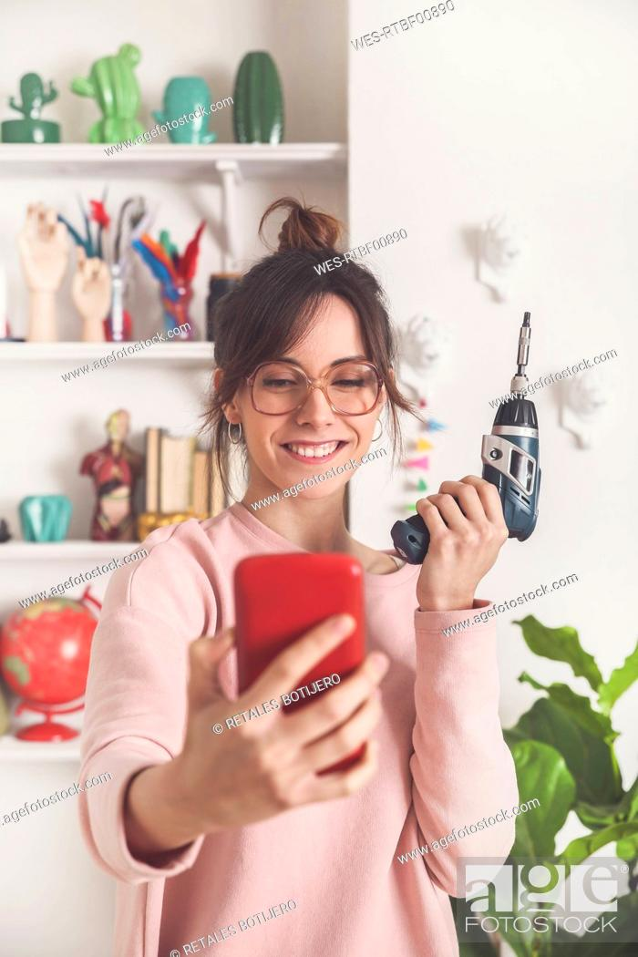 Stock Photo: Portrait of smiling young woman taking selfie with electric screwdriver at home.