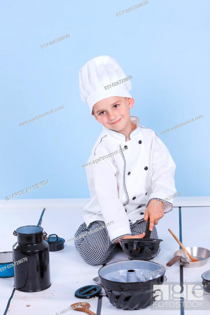 Stock Photo: One little boy as chef cook making salad, cooking with vegetables. Isolated on white.