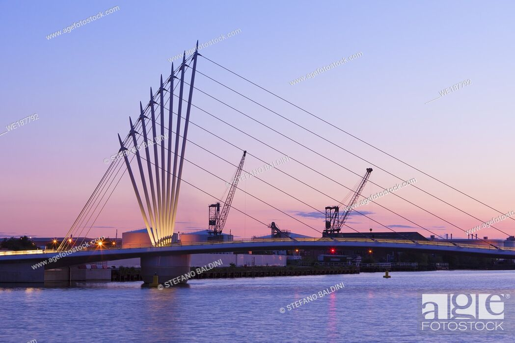 Imagen: Media City footbridge connecting Trafford Promenade with MediaCityUK with the victorian cranes behind that inspired the design, Salford Quays, Manchester, UK.