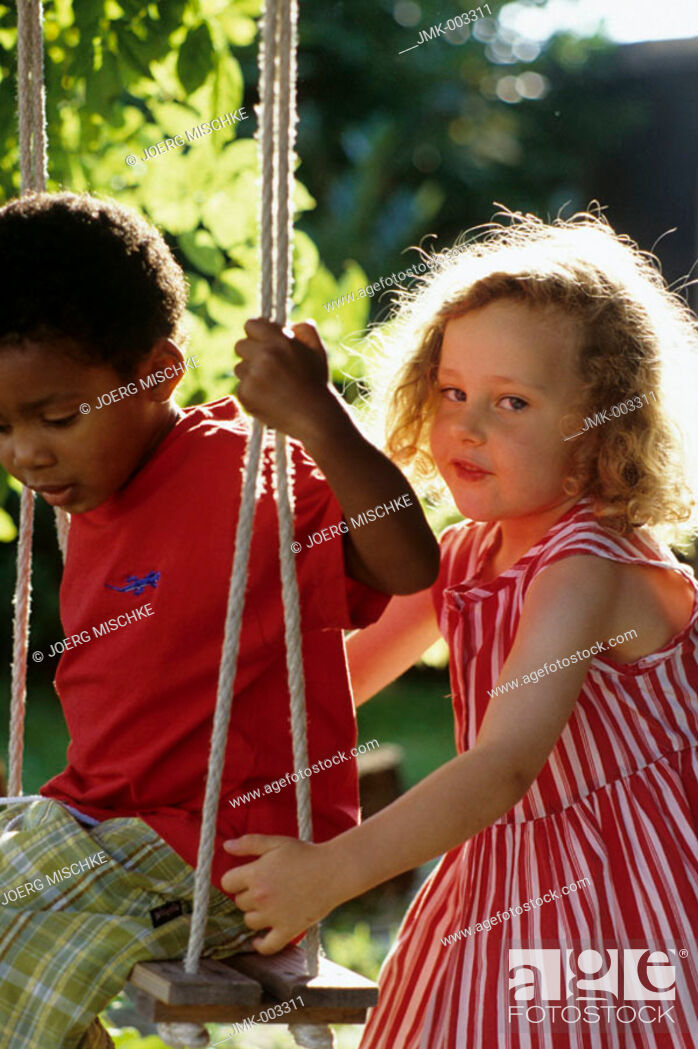 Stock Photo: Two little children, a boy and a girl, 1-5 years old, in the garden in summer, the boy sitting on a swing.