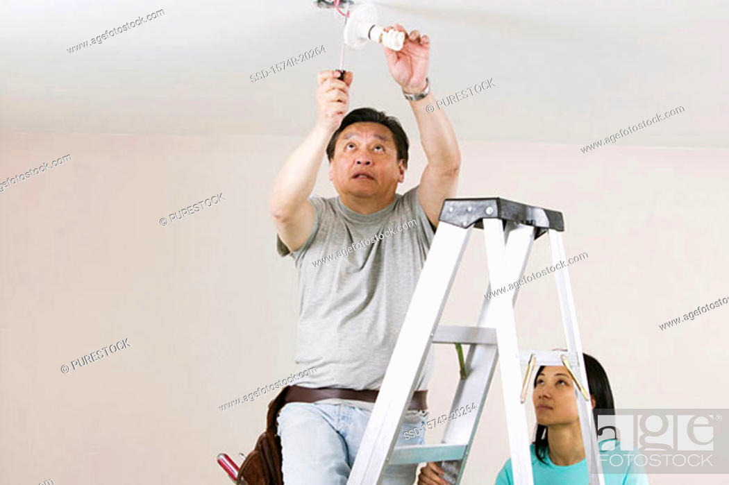 Stock Photo: Low angle view of a mid adult man fixing a light fixture with a young woman holding a ladder.