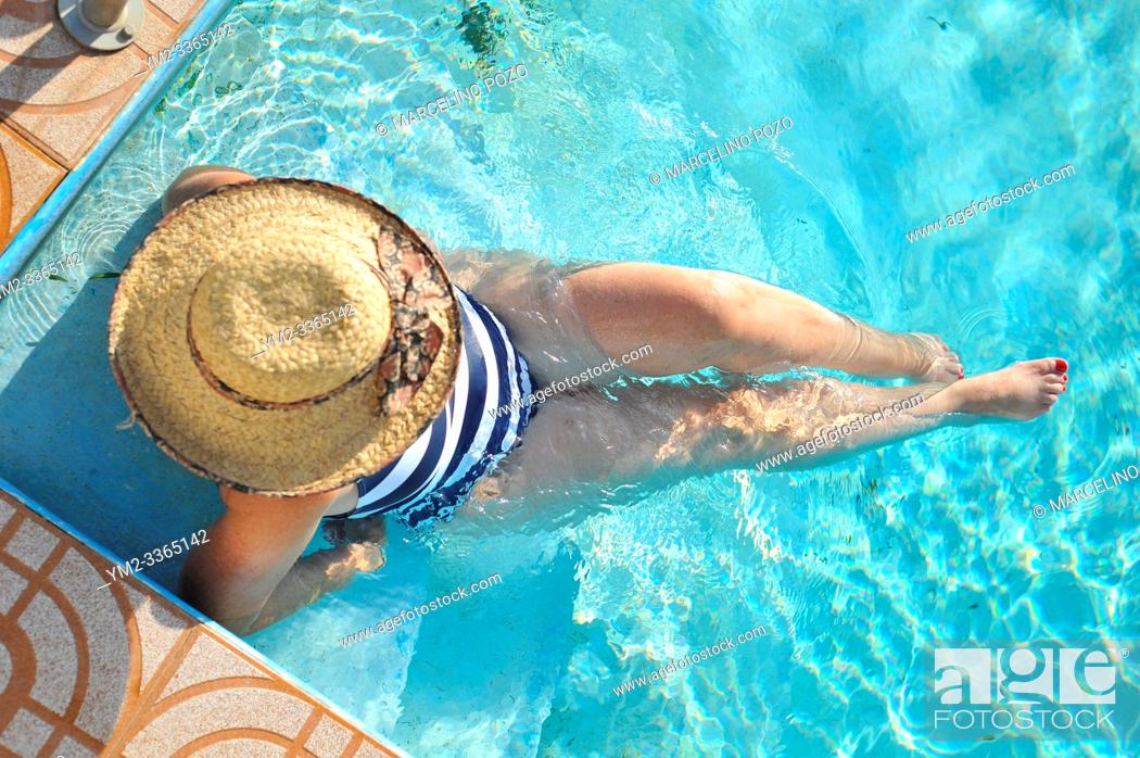 Stock Photo: Woman in a hat resting and enjoying a swimming pool.
