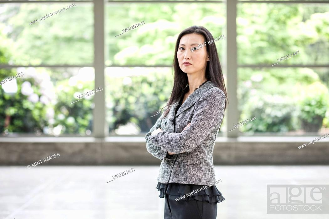 Stock Photo: Portrait of an Asian businesswoman in the lobby of a convention centre.