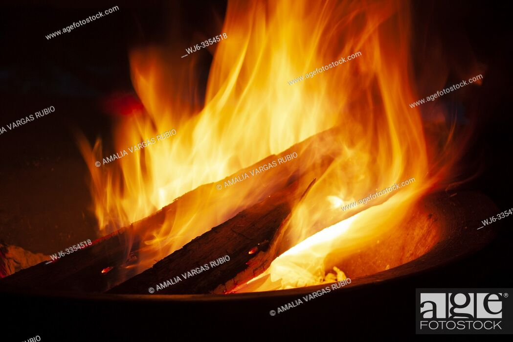 Stock Photo: Approaching logs burning between the flames to fan the fire that illuminates a black night.