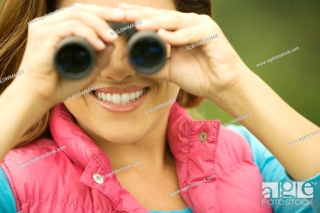 Stock Photo: Close-up of a young woman looking through a pair of binoculars.