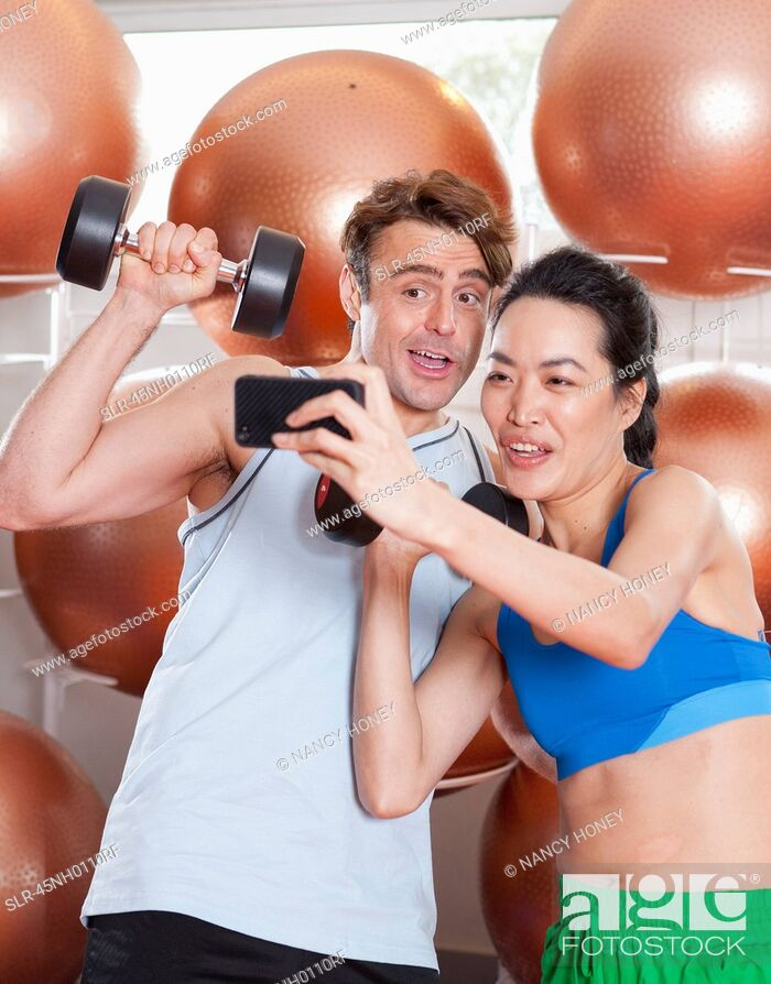 Stock Photo: Couple taking picture together in gym.