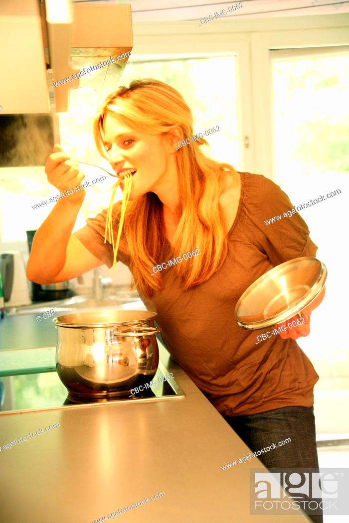 Imagen: Young Woman InThe Kitchen Cooking Pasta.