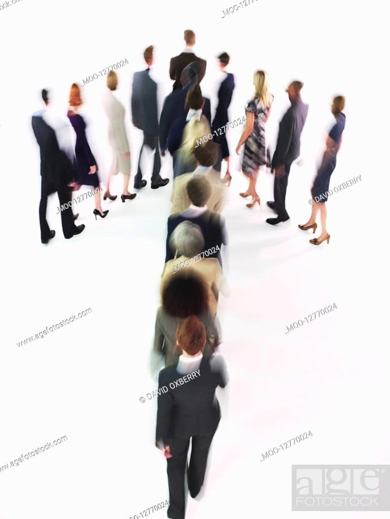 Stock Photo: Group of Businesspeople walking in arrow formation.