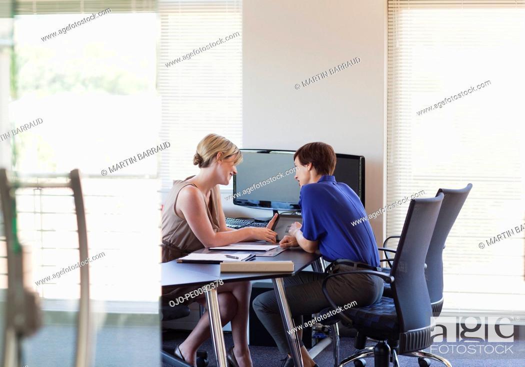 Stock Photo: Businesswomen talking at desk in office.