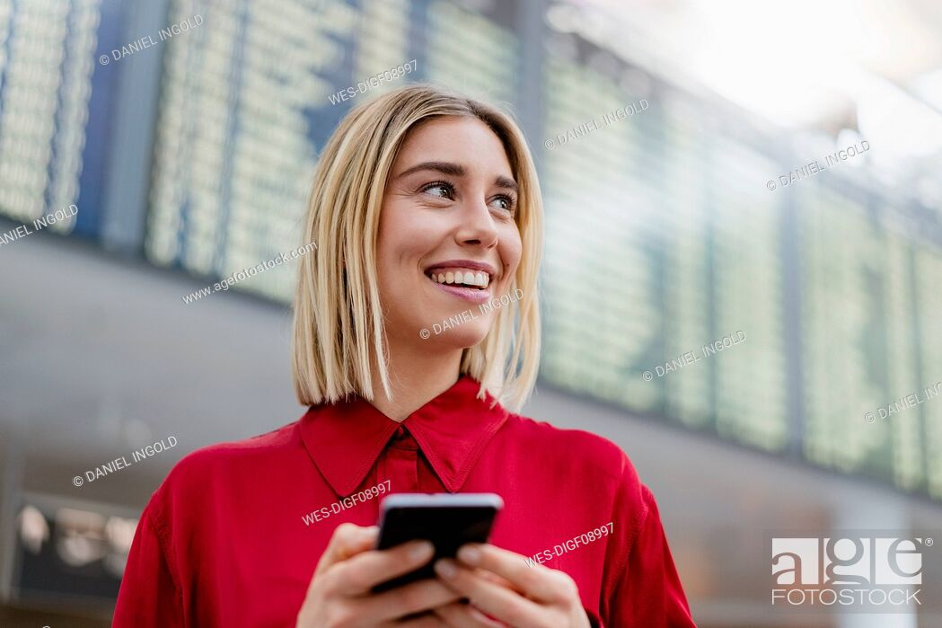 Stock Photo: Smiling young businesswoman with cell phone at arrival departure board at the airport.