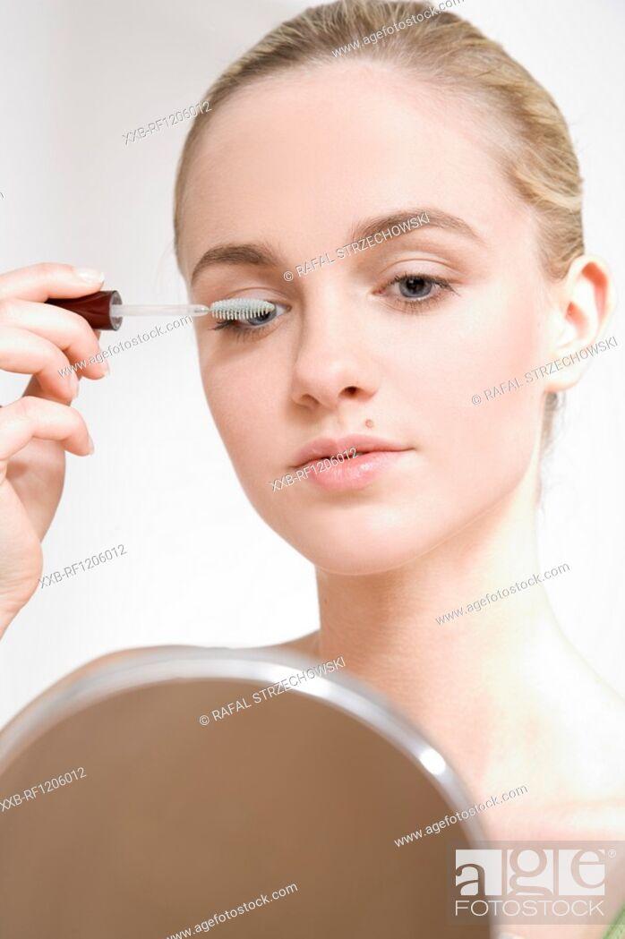 Imagen: young woman applying mascara.