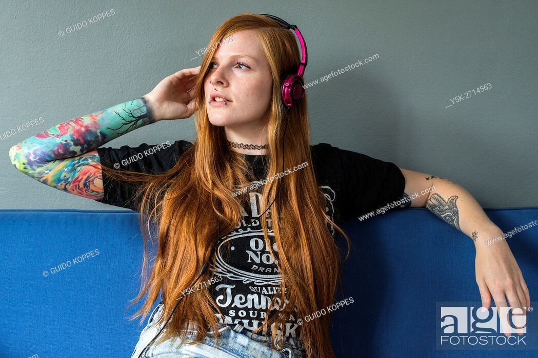 Stock Photo: Tilburg, Netherlands. Young red haired woman listening to her music, uploaded on her smartphone, while relaxing on her living room couch.