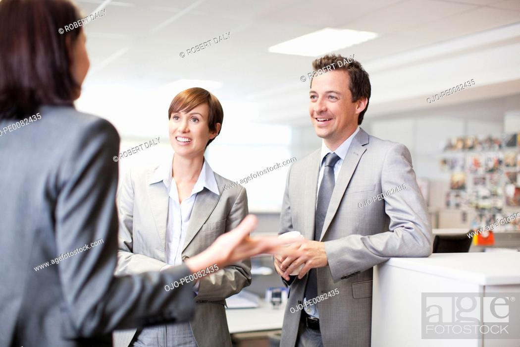 Stock Photo: Smiling business people talking in office.