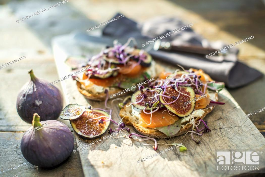 Stock Photo: Salmon sandwiches with figs and sprouts on a wooden board.