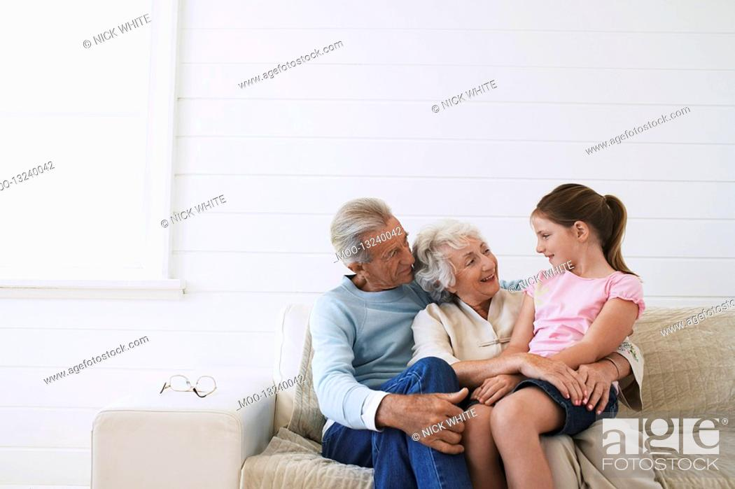 Stock Photo: Senior couple sitting with daughter on couch.
