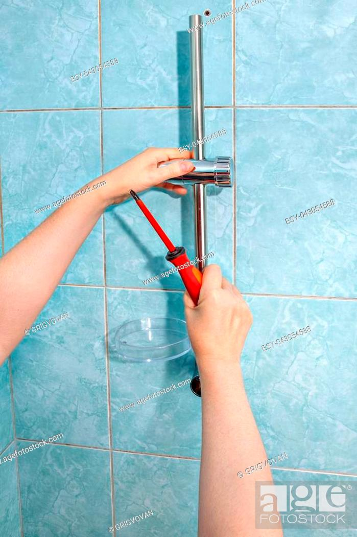 Stock Photo: Residential plumbing repair, close-up install hand held shower head holder.