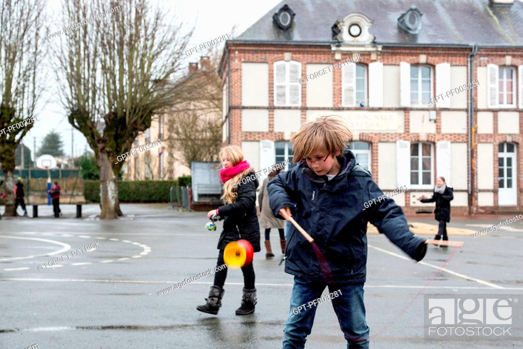 Stock Photo: CHILDREN PLAYING WITH DIABOLOS IN THE SCHOOLYARD OF THE PRIMARY SCHOOL OF RUGLES (27), FRANCE.