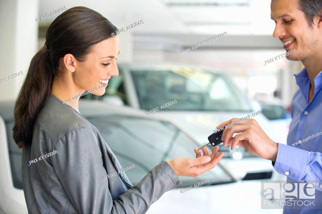 Stock Photo: Happy salesperson handing woman car key in showroom.