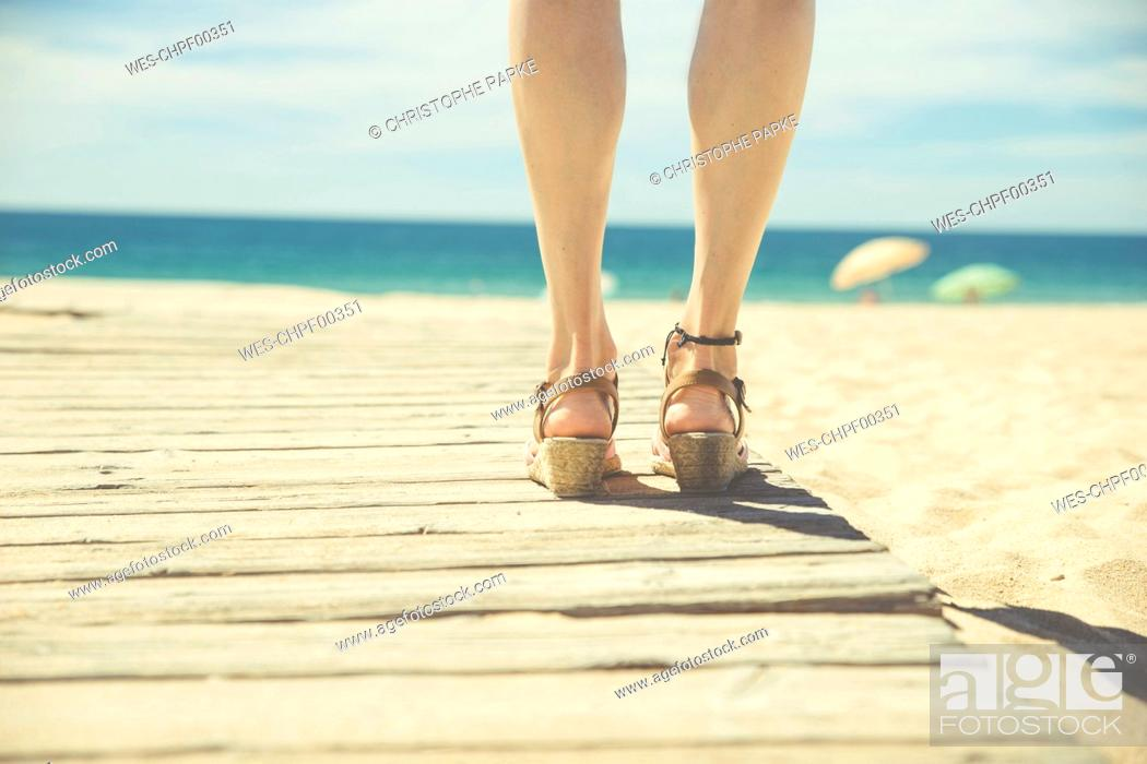 Stock Photo: Legs of woman standing at boardwalk on the beach.